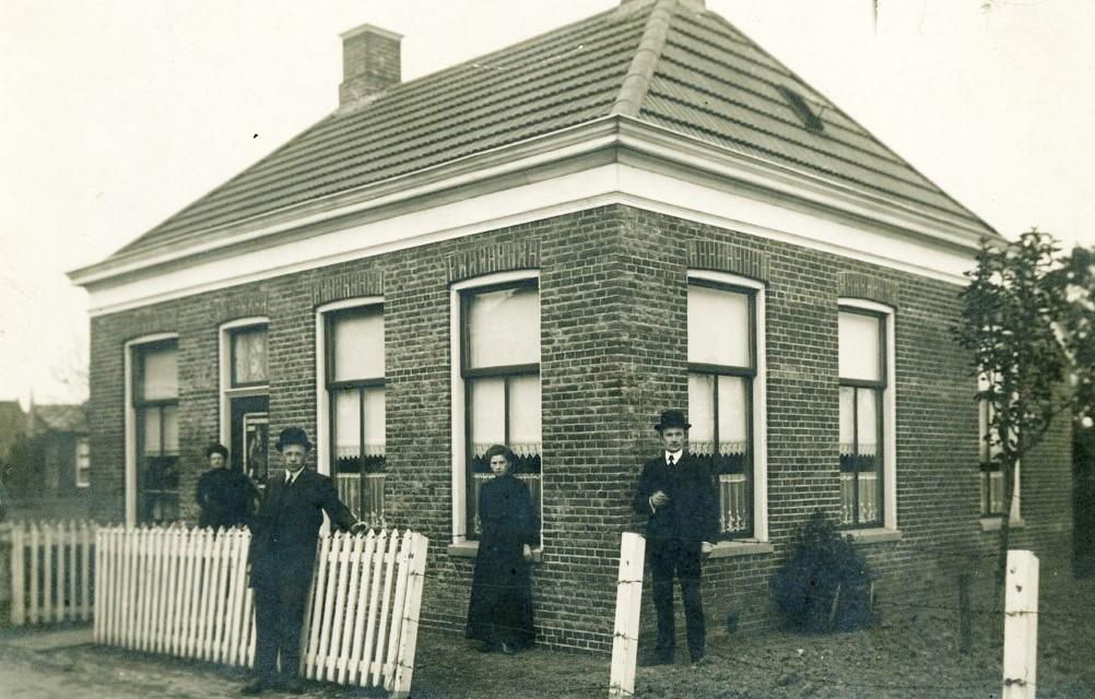 De woning van de fam. Apol omstreeks 1910. Op de foto vlnr. Trientje Apol, Johannes Apol, Bouwina Apol en Jan Apol.